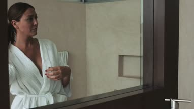 Woman standing in front of mirror and adjusting bathrobe  man taking shower in background