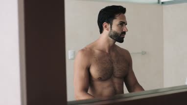 Man standing in front of mirror and adjusting hair in bathroom