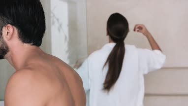 Man touching his beard  woman in bath robe standing in background