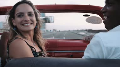 Young man and woman sitting in convertible and dancing, enjoying road trip