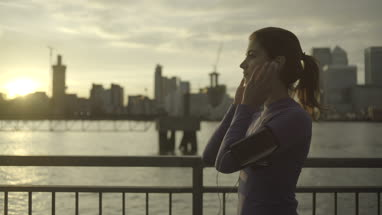 Female runner with headphones jogging by Thames River, London