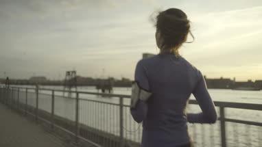 Female runner jogging by river Thames, London
