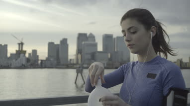 Female runner drinking water by river Thames, London