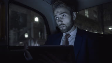 Young adult business male in taxi using digital tablet at night