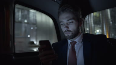 Young adult business male in taxi using smart phone