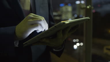 Close up hand of Business male on digital tablet in evening at business district