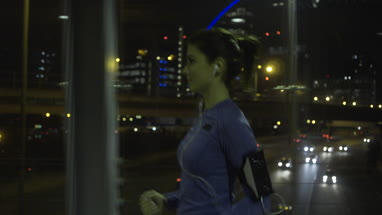 Young adult female jogging in city at night