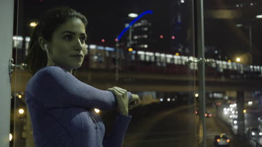 Young adult female runner stretching in city at night
