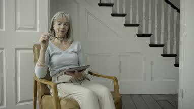 Senior Adult Female reading on digital tablet
