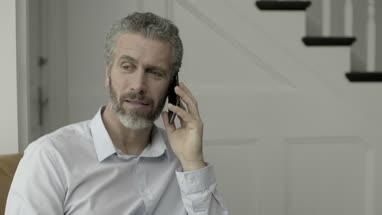 Mature Adult Male working from home on the phone