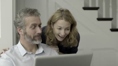 Senior Adult couple working from home on laptop