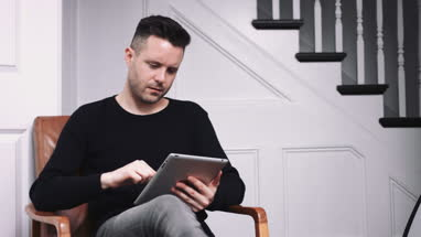 Adult male working on digital tablet at home