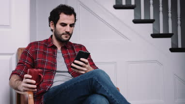 Adult male working on smart phone and drinking coffee at home