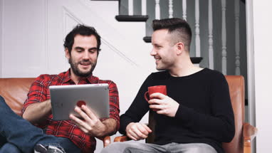 Same sex couple watching pictures on digital tablet and drinking coffee