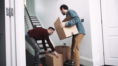 Same sex couple moving in new house carrying boxes