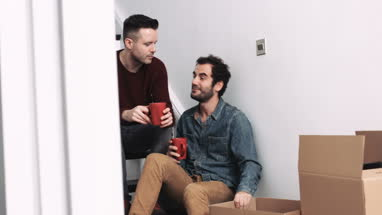 Same sex couple moving in new house, drinking coffee