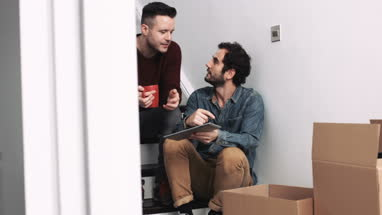 Same sex couple moving in new house, drinking coffee, using digital tablet