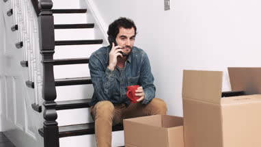 Adult man working on smart phone at home and moving house