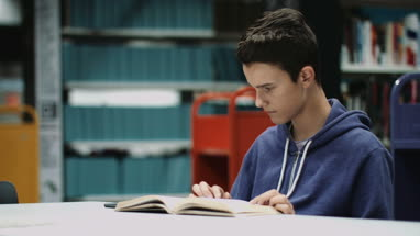 Teenage boy studying book in library