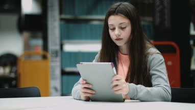 Teenage girl working on digital tablet in library