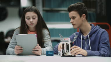 Teenage boy and girl working with digital tablet and robot in library
