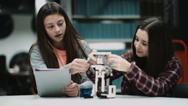 Teenage girls working with digital tablet and robot in library