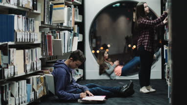 Teenage girls and boy studying in library