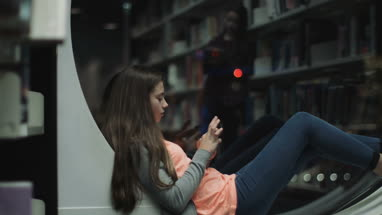 Teenage girl studying in library with smart phone, night time