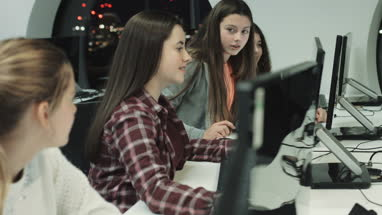Teenage girls working on computer in technology class