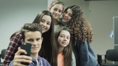 Teenage girls and boy making selfie on smart phone