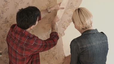 Adult couple home improvement taking of wallpaper