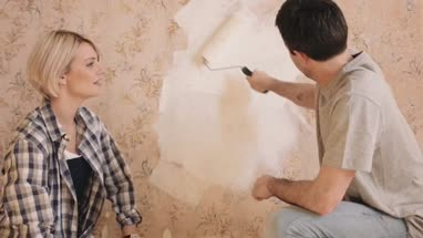Adult couple painting wall in new home