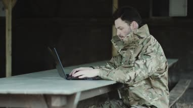 Army soldier on laptop at base camp
