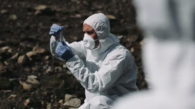 Forensic scientist examining sample at river bank