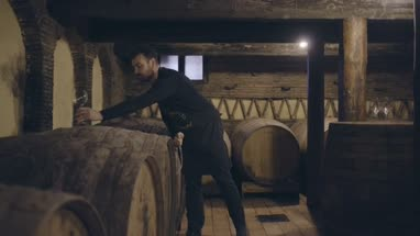 Farmer pouring wine from barrel