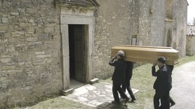 Pallbearers walking into church with coffin