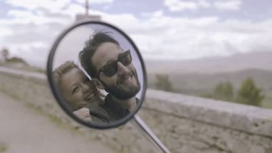 Reflection in side mirror of couple kissing