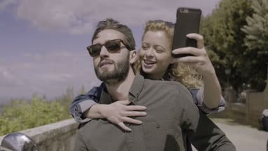 Couple on scooter taking selfie