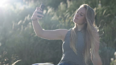 Young adult female taking selfie in nature