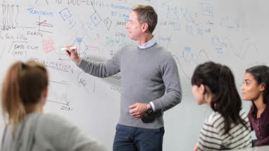 Professor teaching with whiteboard notes