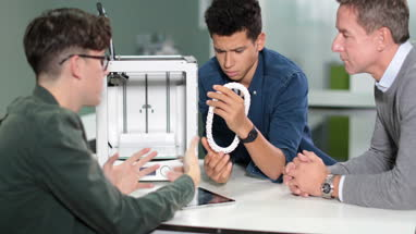 Students discussing 3D printer with teacher
