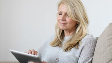 Mature woman at home using digital tablet