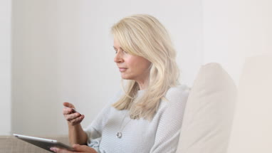 Mature woman at home using digital tablet and credit card
