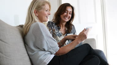 Mature female friends looking at digital tablet