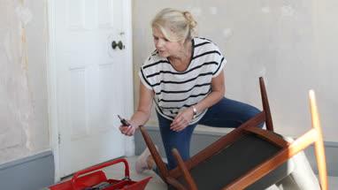 Mature female repairing an old chair
