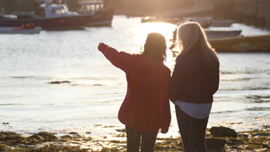 Mature female friends talking in harbour