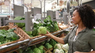 Woman buying vegetables in grocery store