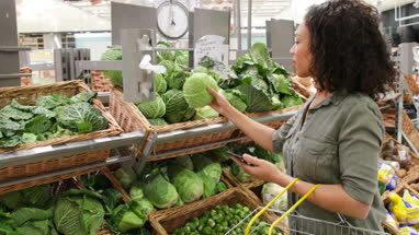 Woman in grocery store using smartphone