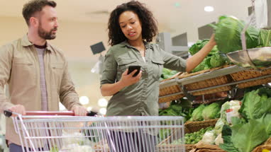 Couple buying in grocery store using smartphone