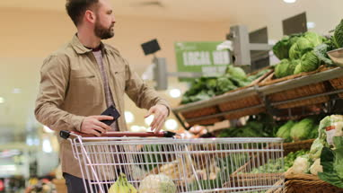 Man in grocery store using smartphone